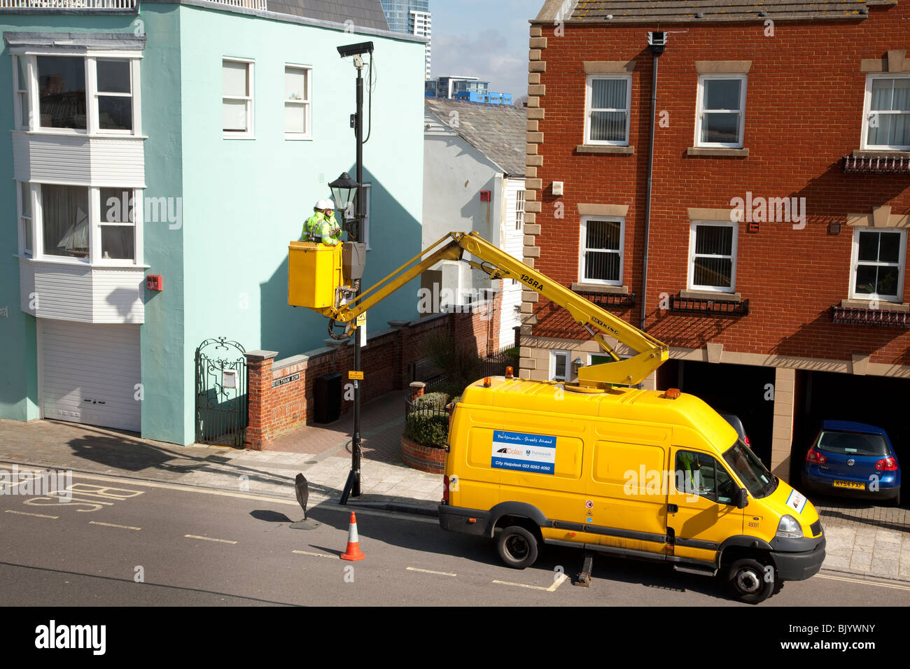 street furniture maintenance workers using a cherry picker van to maintain street lights - Stock Image