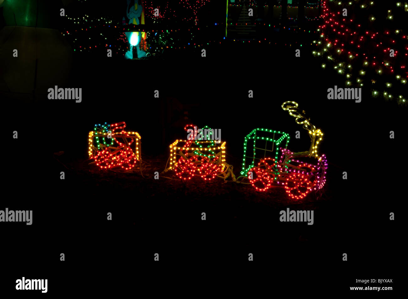 this little toy train is in christmas lights at night against a dark background with other