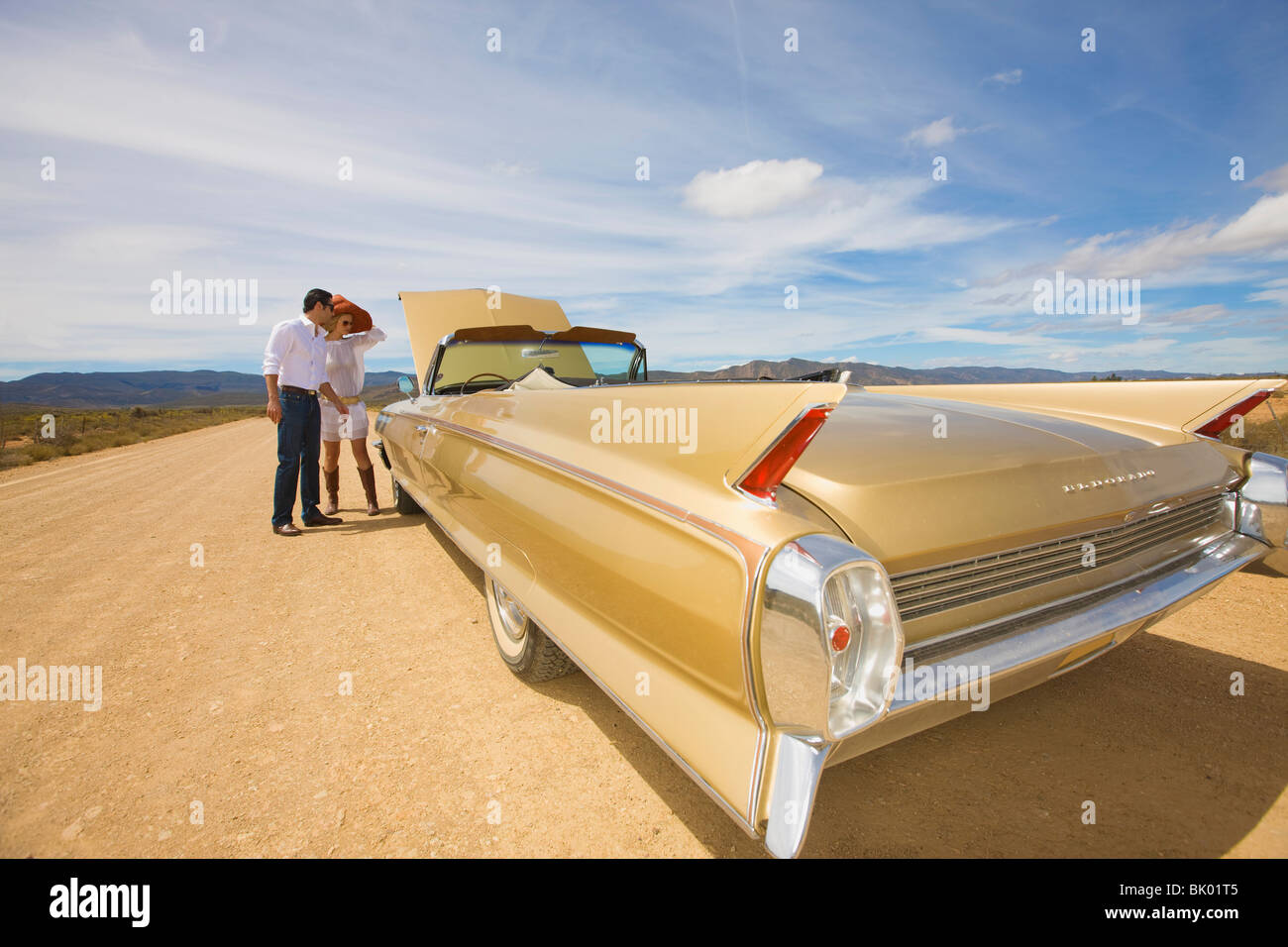 Couple with car trouble in desert - Stock Image