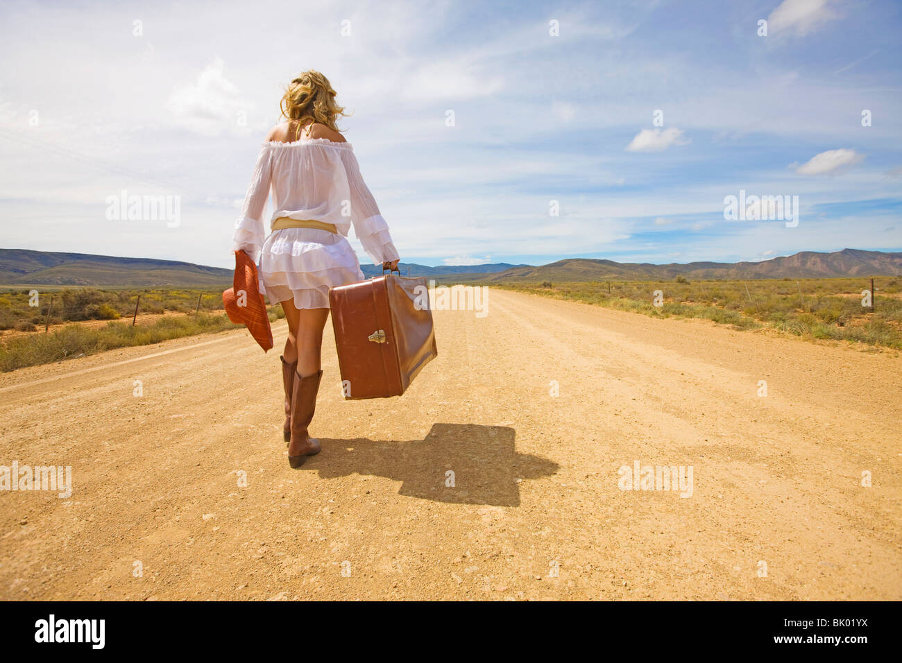 Lonely woman on desert road - Stock Image