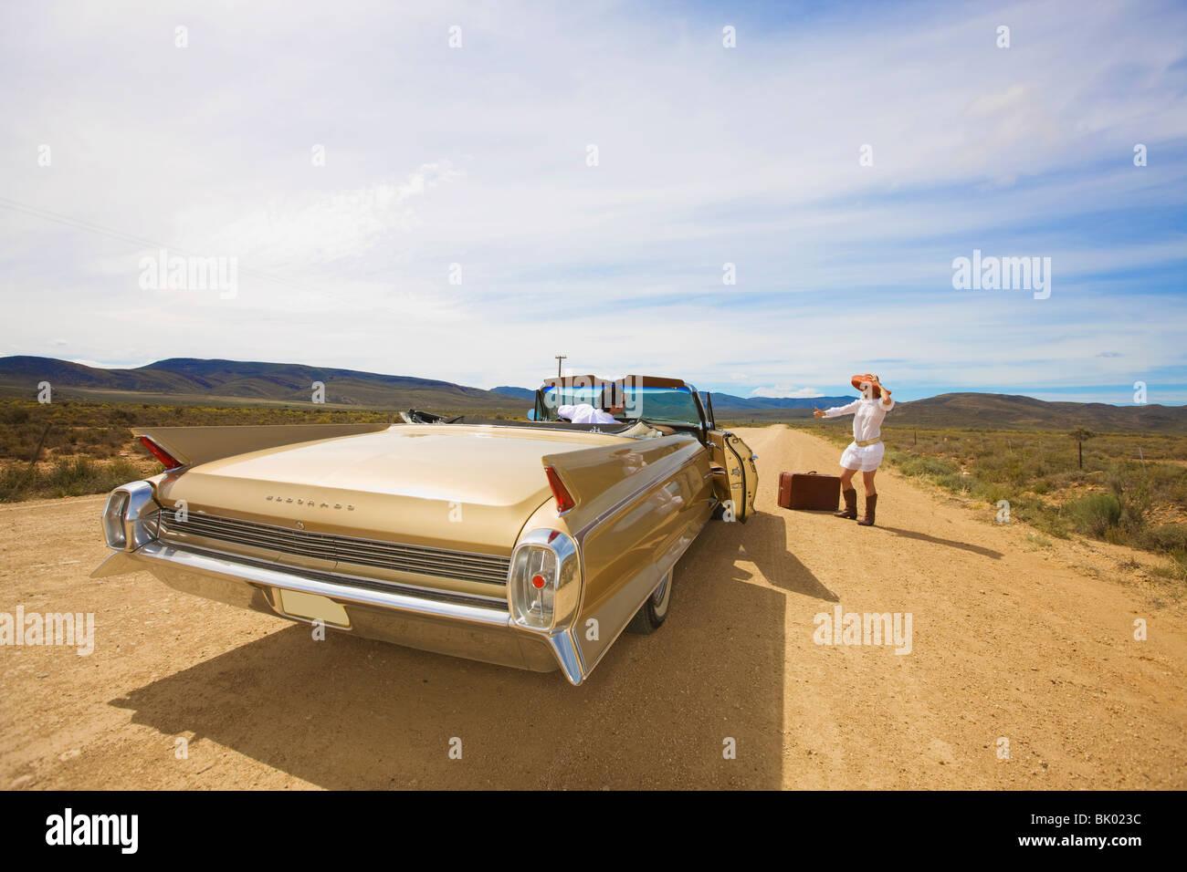 Woman hitching on desert road Stock Photo