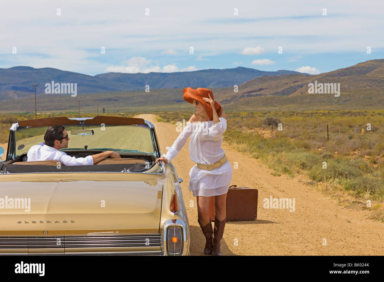 Woman hitching on desert road - Stock Image