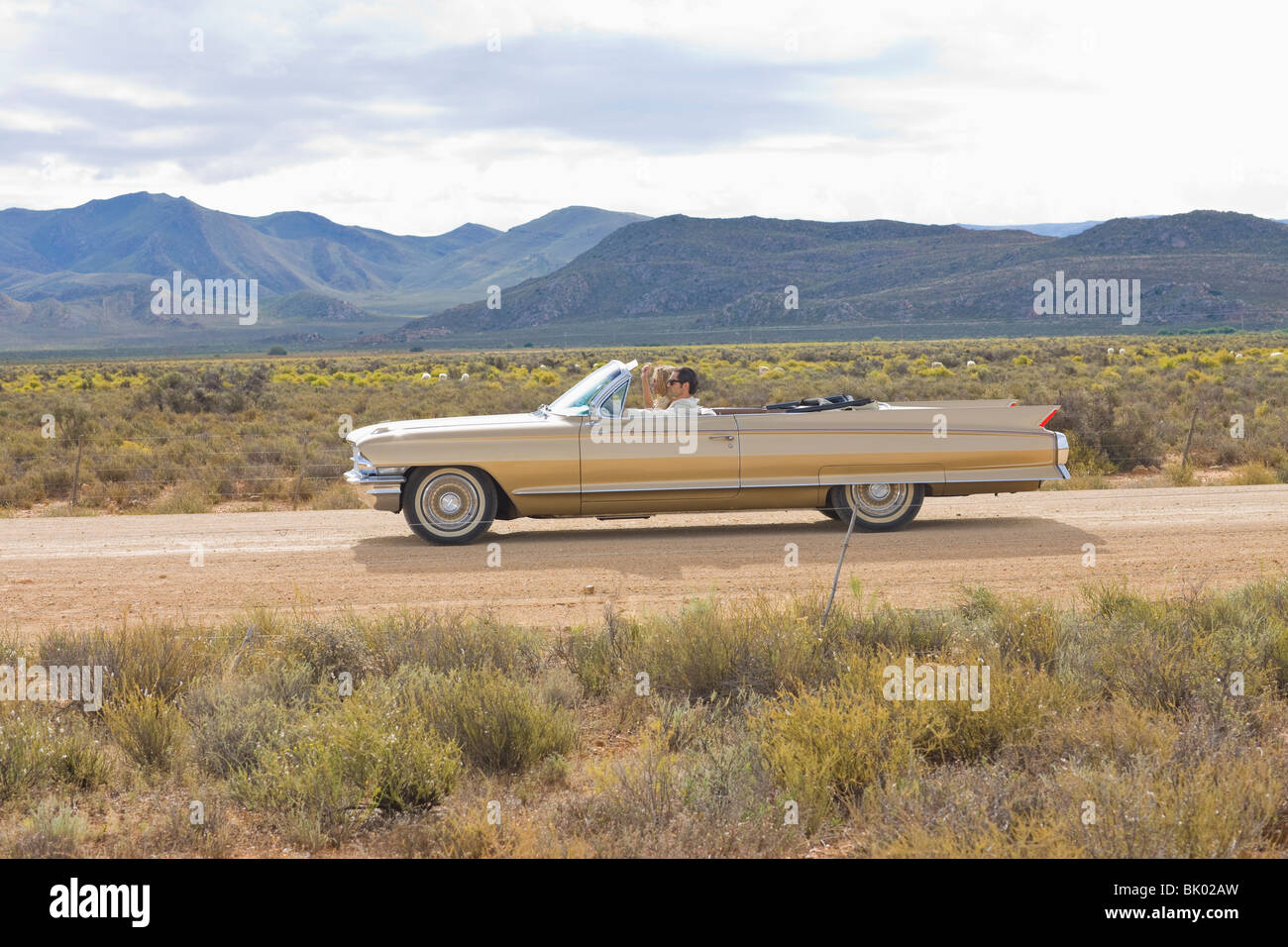 Couple driving trough desert - Stock Image