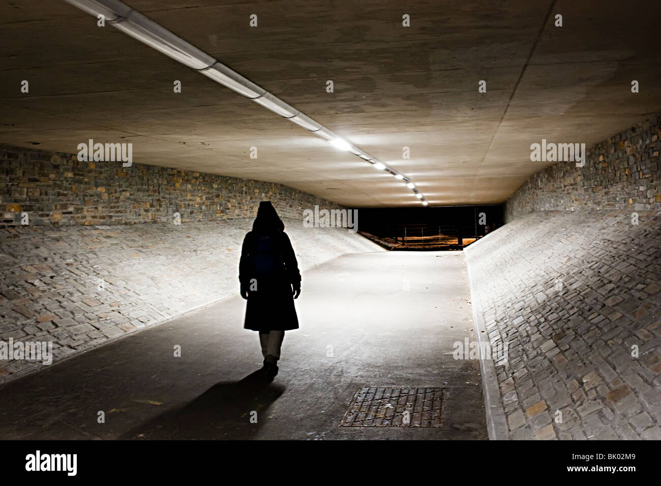 Woman walking alone through underpass at night Abergavenny Wales UK - Stock Image