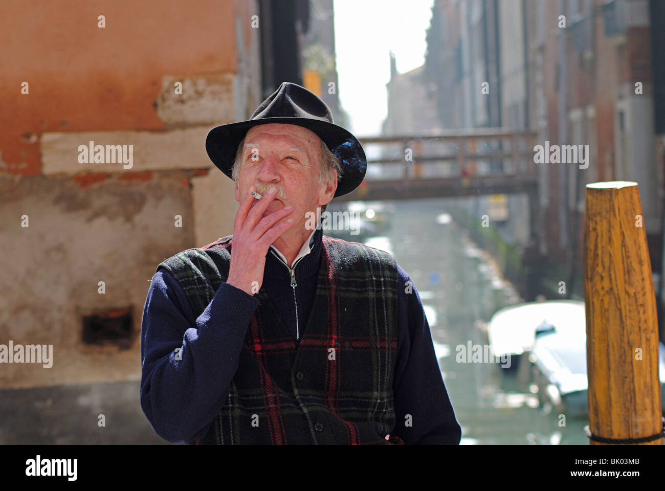 An elderly Italian man smokes a cigarette beside a canal in Venice, Italy - Stock Image