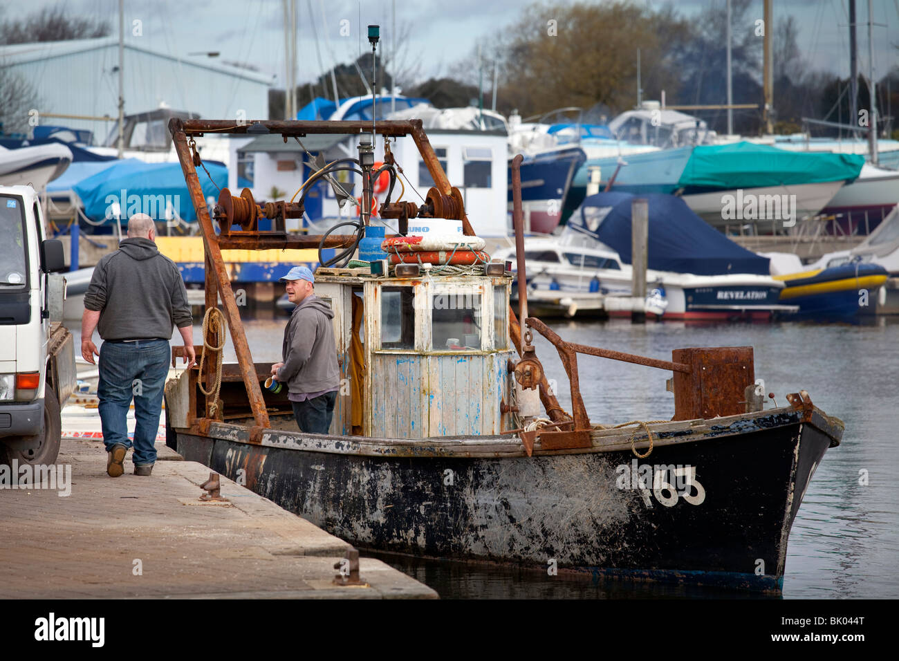 fisherman preparing a stern-trawler / shellfish dredger for inshore/coastal work - Stock Image