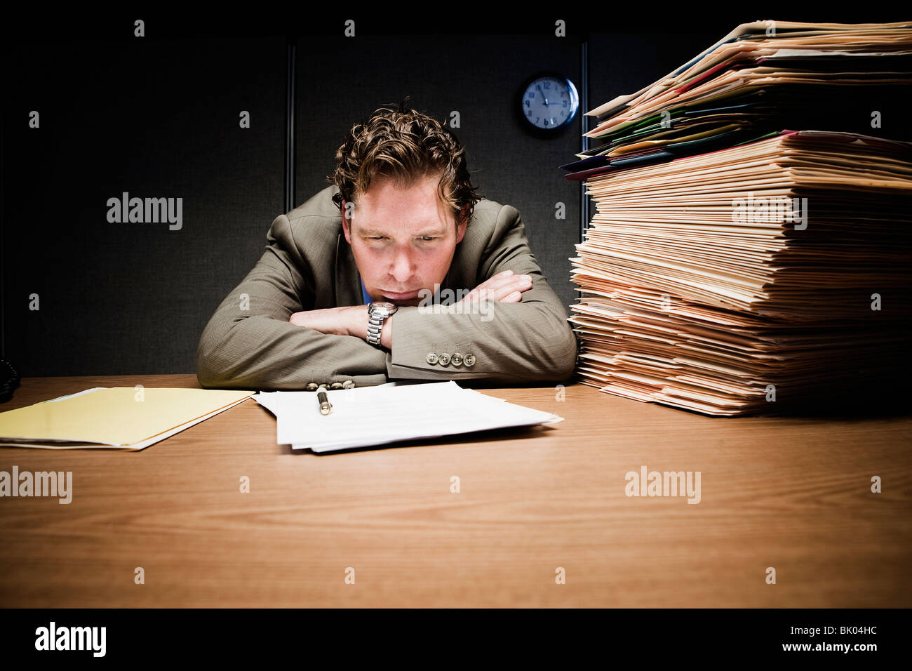 Stressed man with head down on desk - Stock Image
