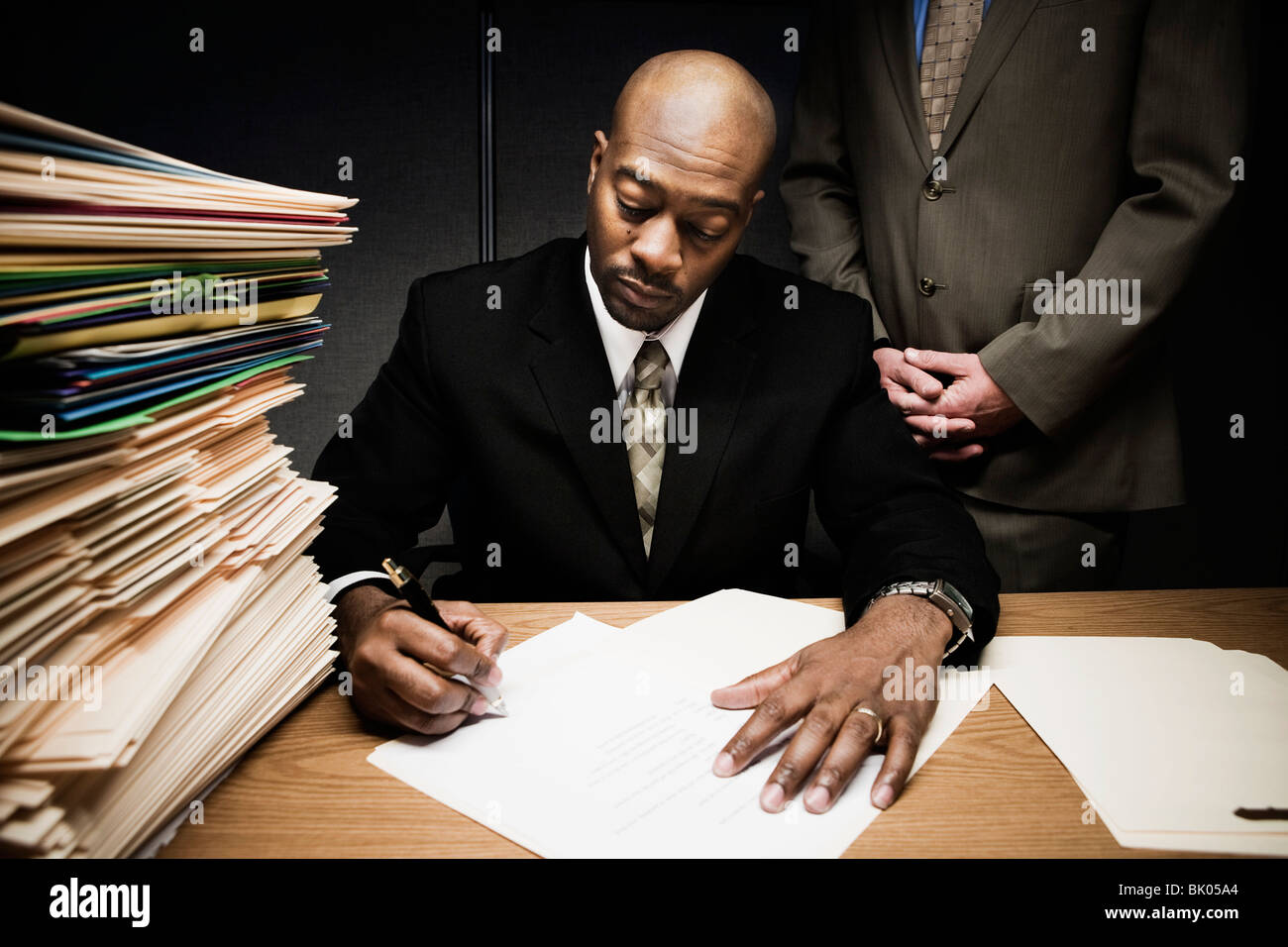 Man doing paperwork with man behind him - Stock Image