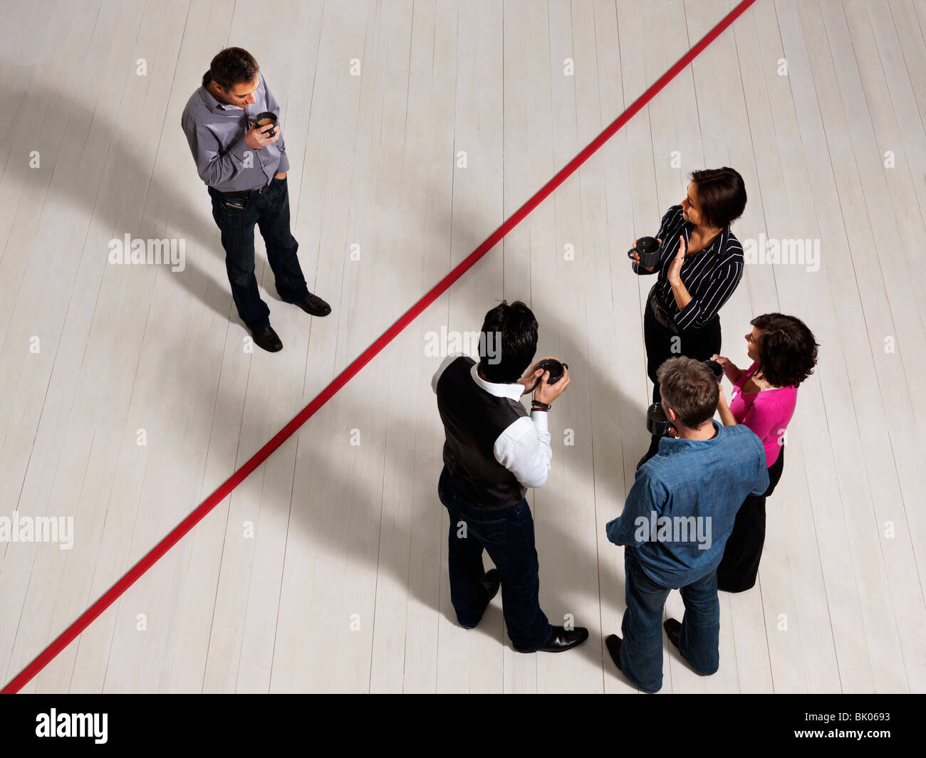Business men and women by red line - Stock Image