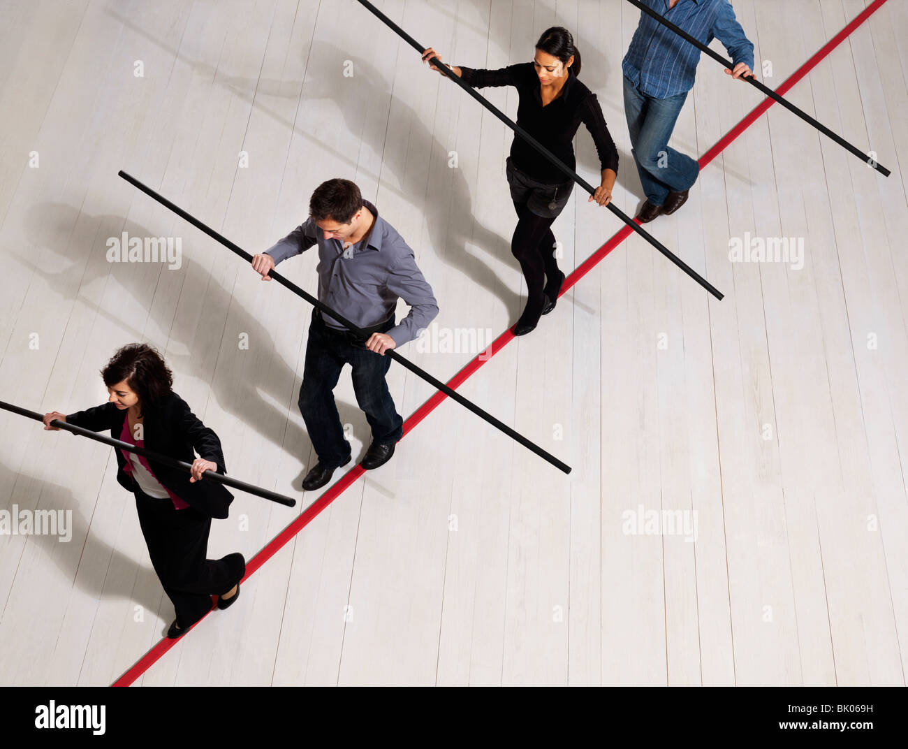 People balancing on thin red line - Stock Image