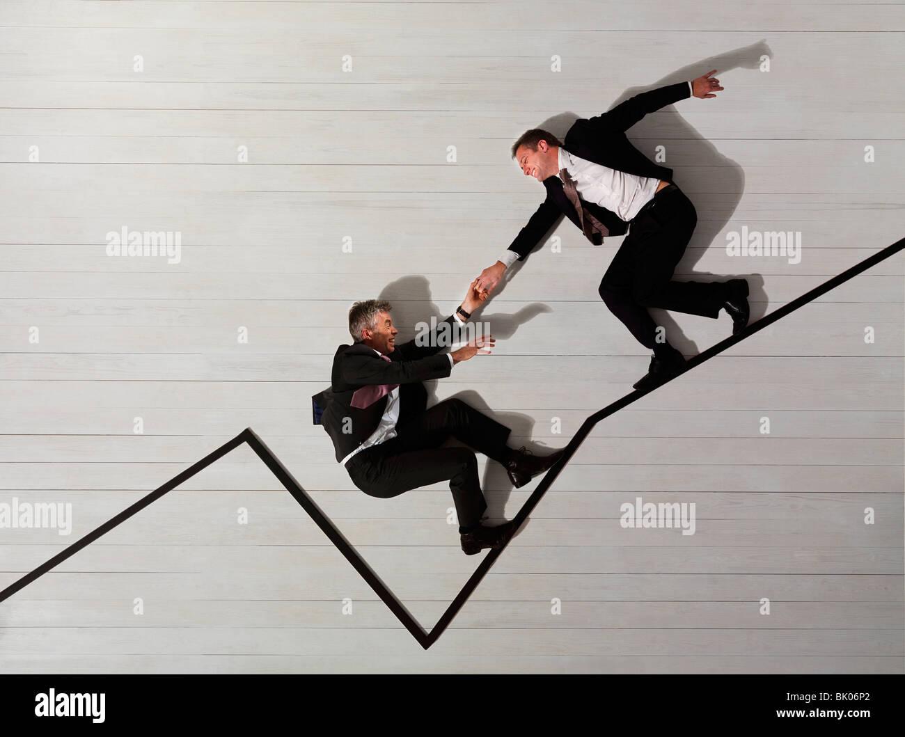 Business men climbing up graph - Stock Image