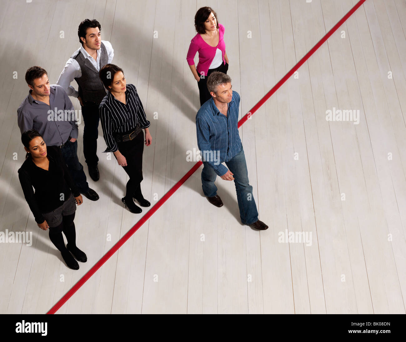 Business men and women crossing red line - Stock Image