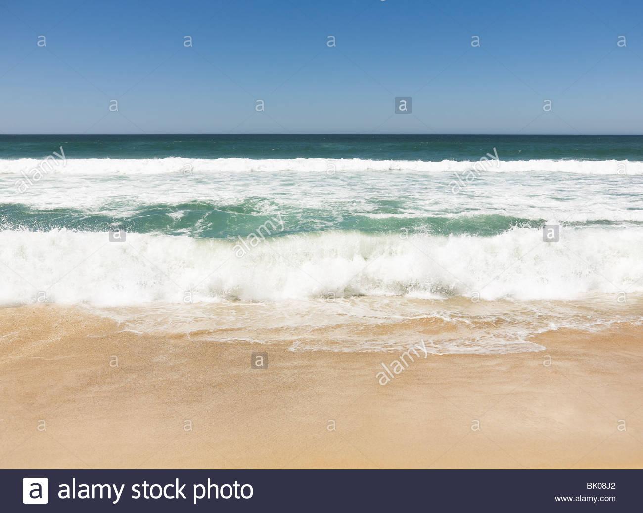 Waves breaking onto beach - Stock Image