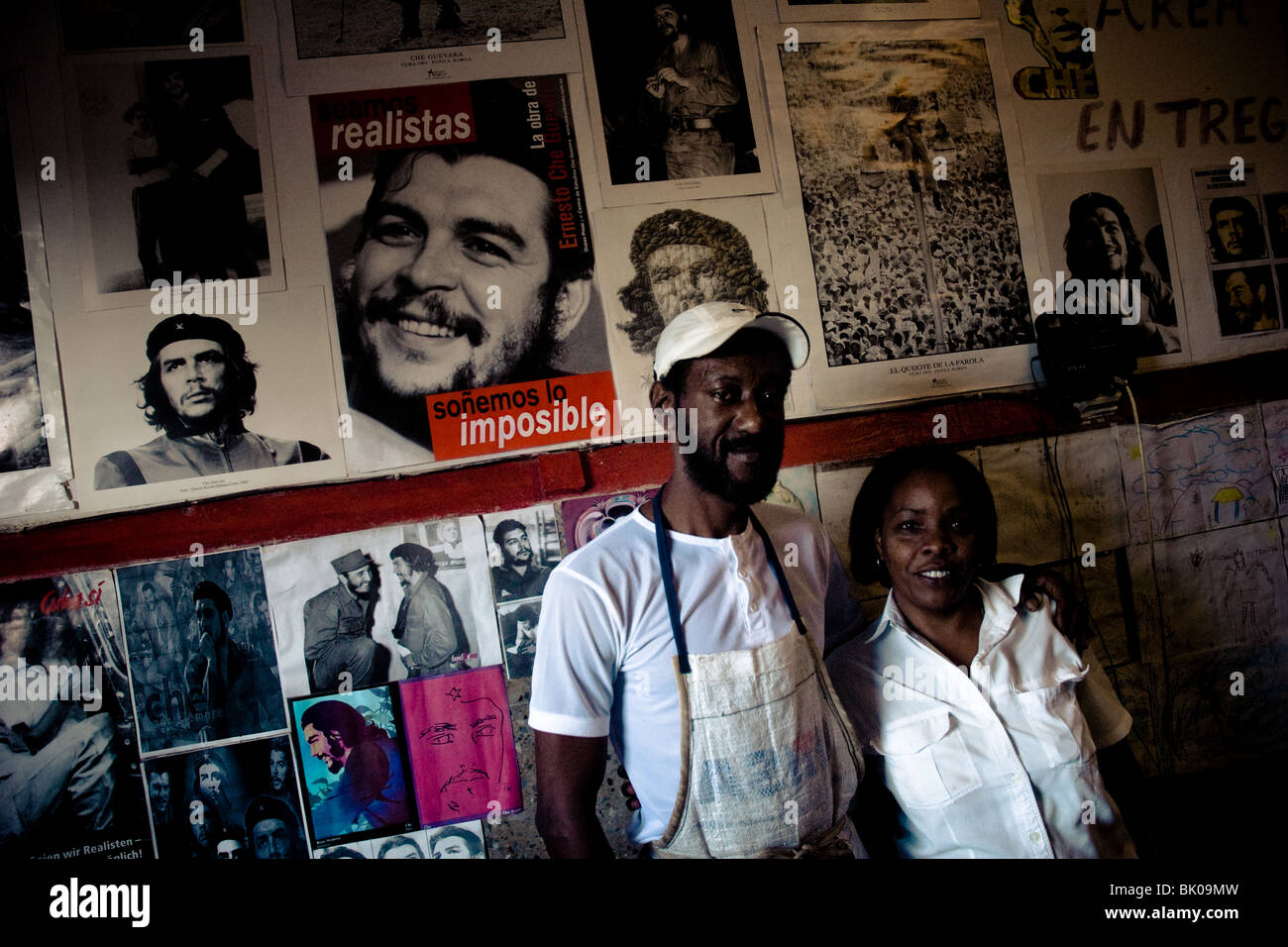 A Cuban bakery employees stand in front of a wall covered by pictures of the Revolutionary leader Che Guevara, Alamar, - Stock Image
