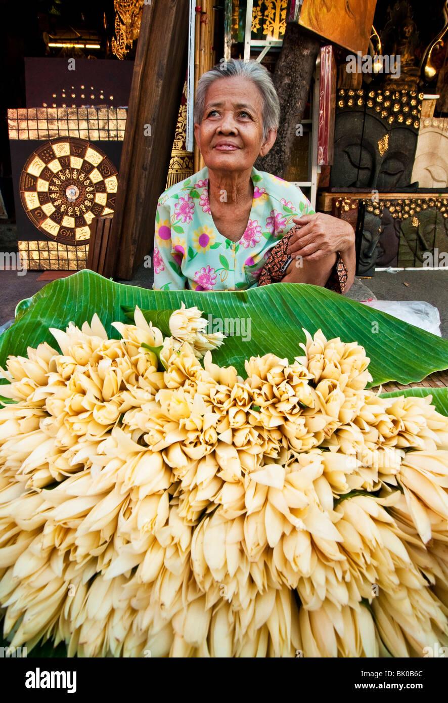 Woman selling flowers in Chatuchak Weekend Market in Bangkok, Thailand. - Stock Image