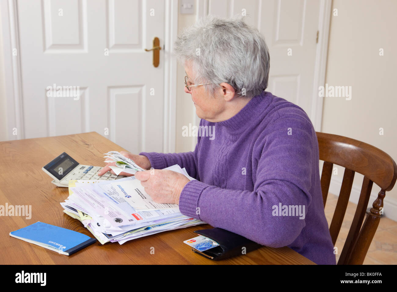 UK Senior woman pensioner with a big pile of bills on the table checking receipts for a credit card bill using a - Stock Image