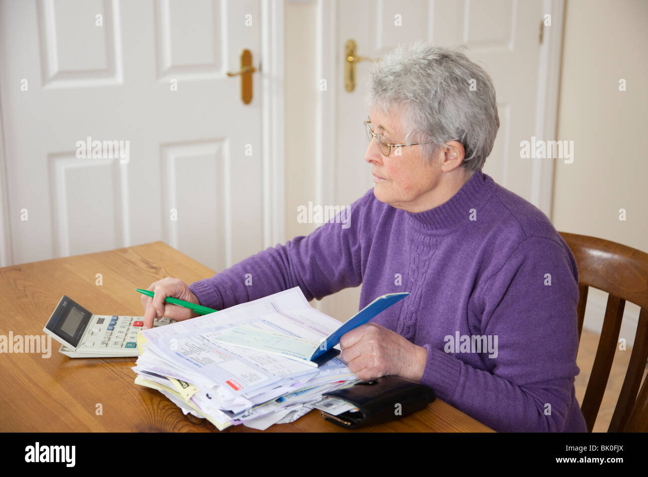 Independent senior woman pensioner with big pile of bills on table using a calculator before writing cheque to pay - Stock Image
