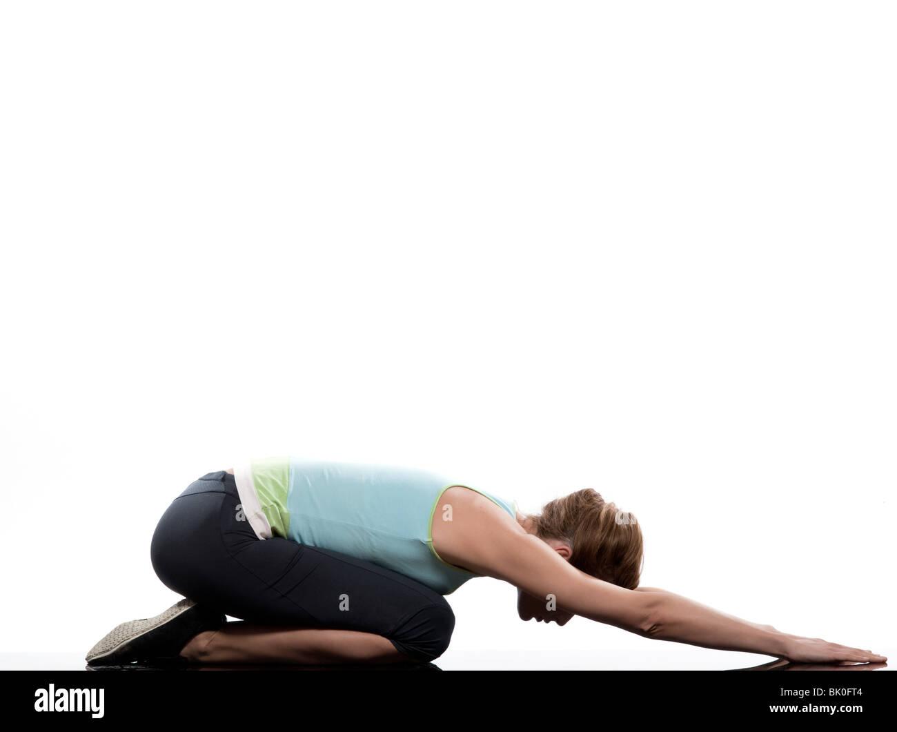 woman adho mukha virasana child pose yoga stretching workout posture on studio white background - Stock Image