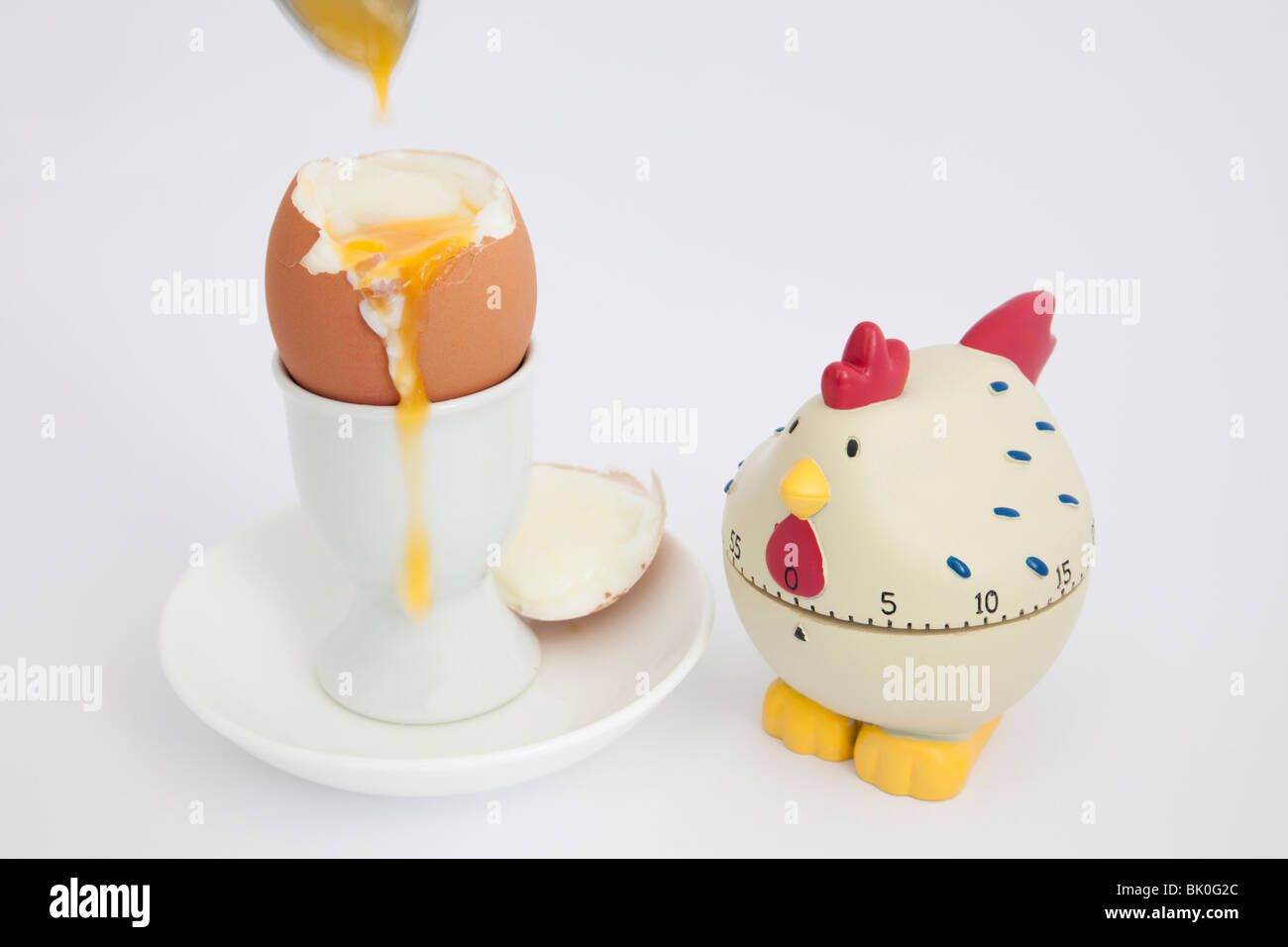 Chicken egg timer with an open soft boiled egg with runny yolk in an egg cup on a white background - Stock Image