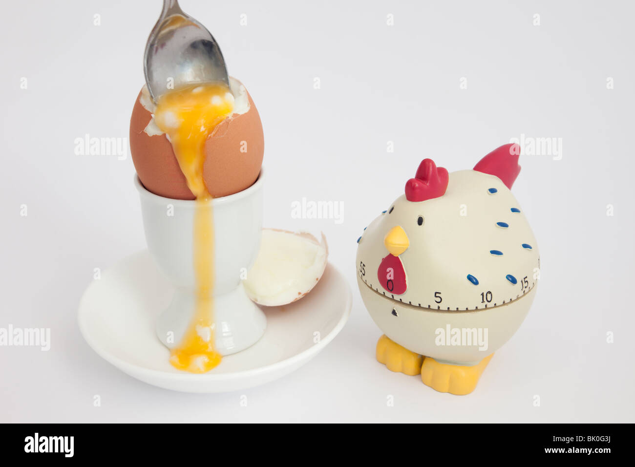 Spoon in an open soft boiled egg with runny yolk in an egg cup with a chicken egg timer on a white background Stock Photo
