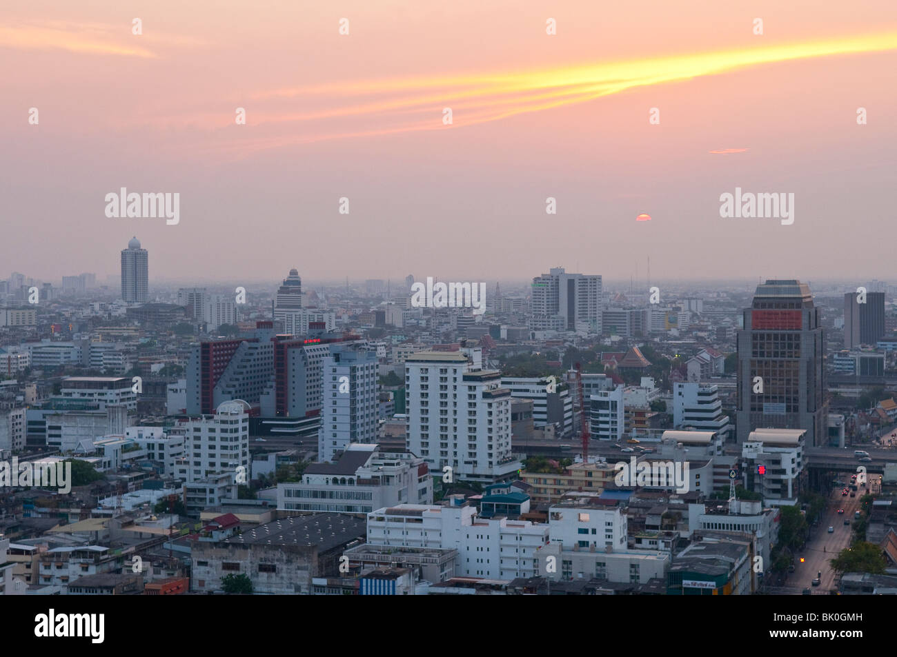 Sunset over downtown Bangkok with haze for agricultural burning; from rooftop restaurant of the Siam@Siam Hotel, - Stock Image