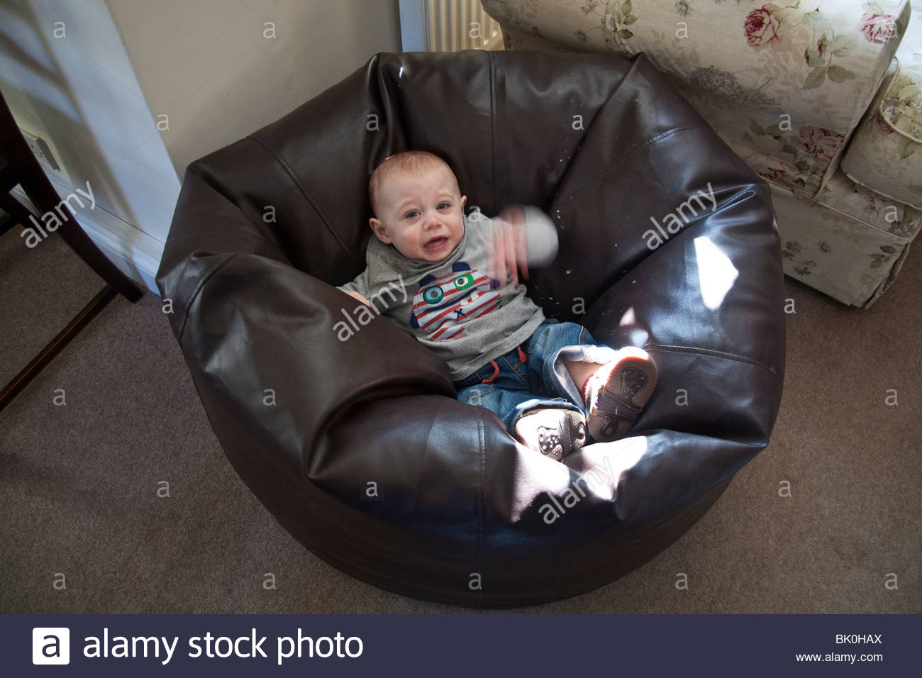 baby boy (11 months old)playing on a large leather cushion. - Stock Image