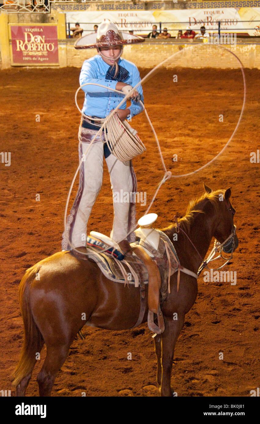 Guadalajara, Mexico, Charro (Cowboy) Trick Roper standing on horse  performing at the Charreda Festival & Rodeo Show, Lienzo