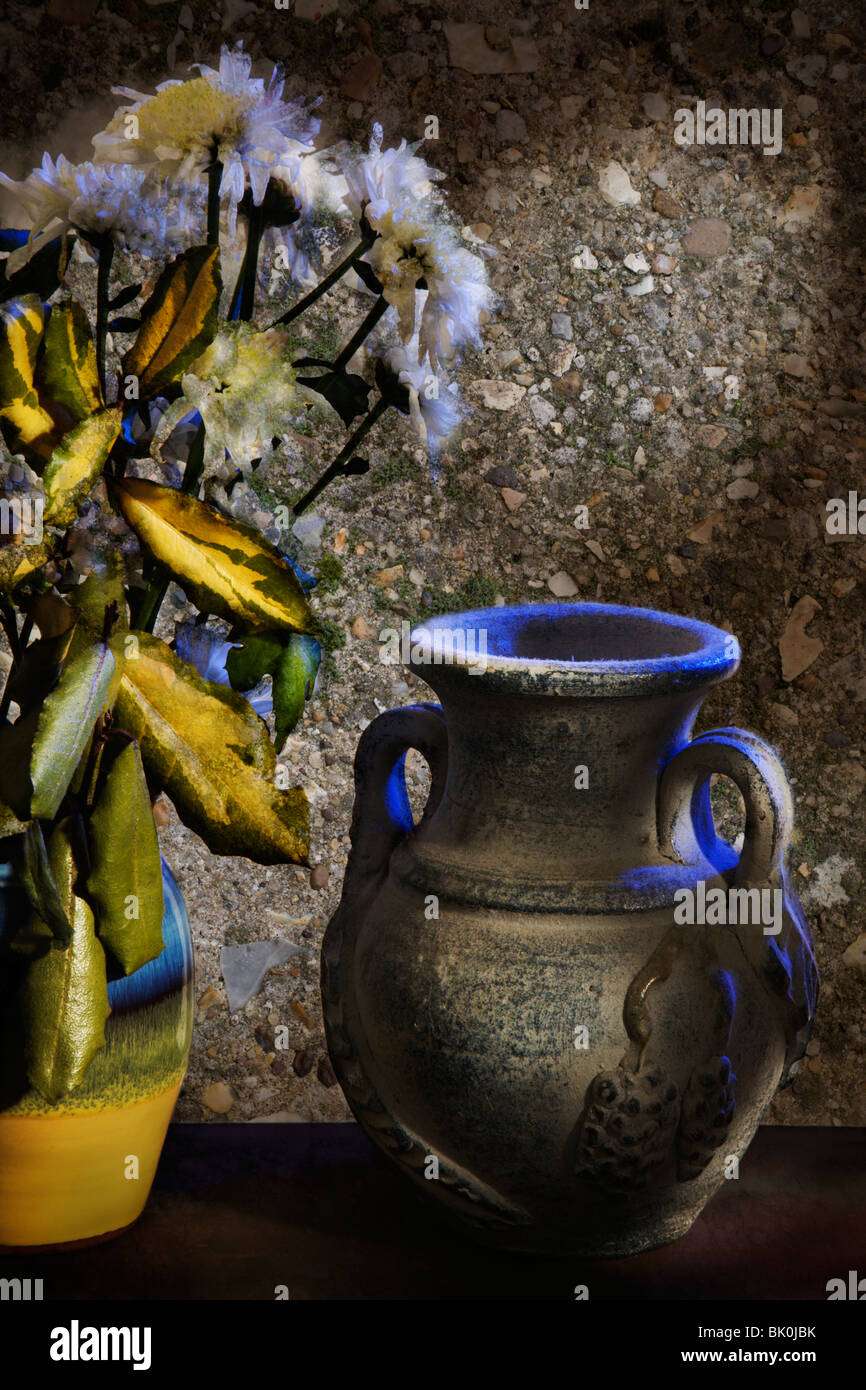 A Spanish pot next to old flowers. - Stock Image