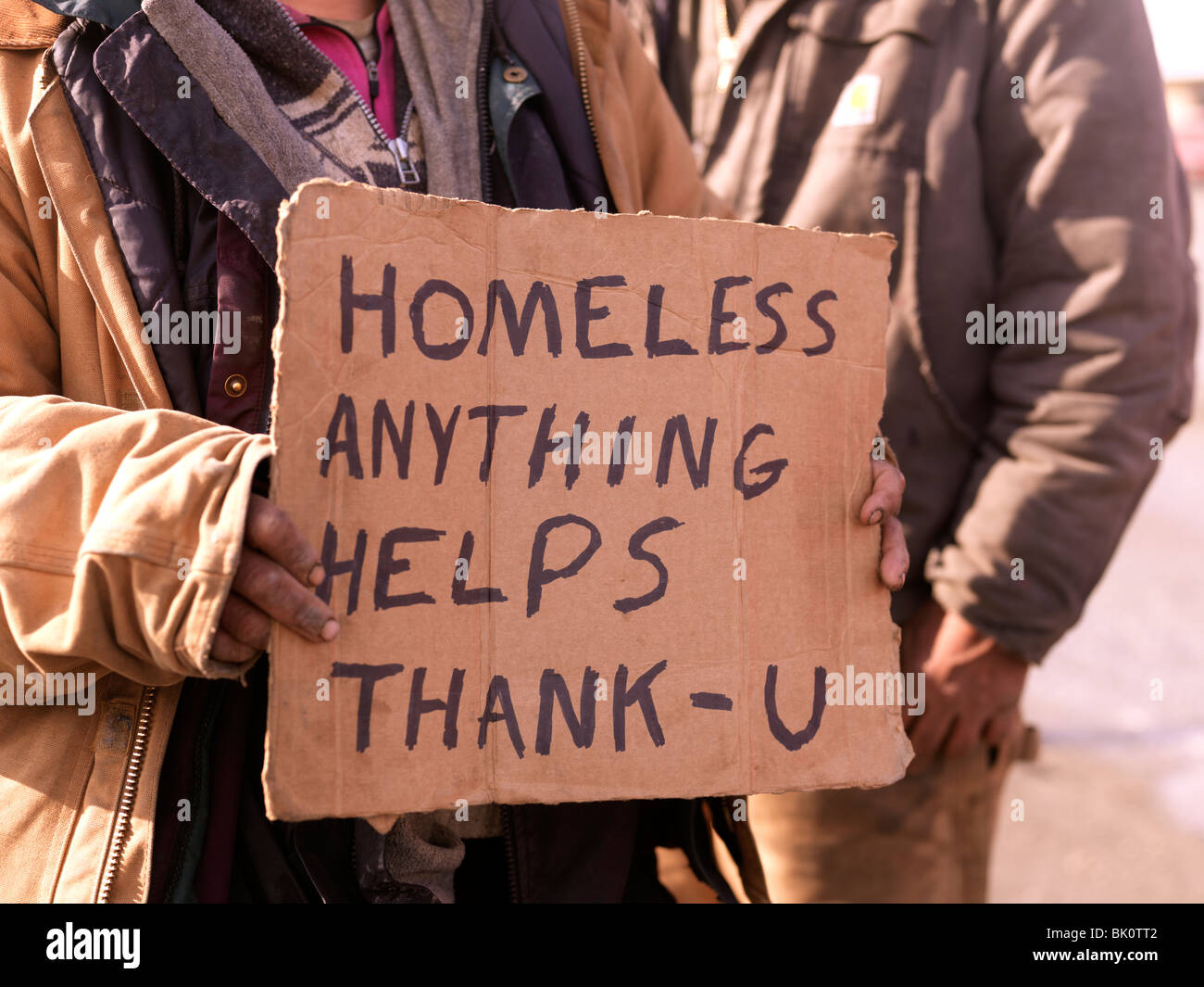 Homeless persons holding sign asking for help and handouts, unemployed and homeless the American recession is tough - Stock Image