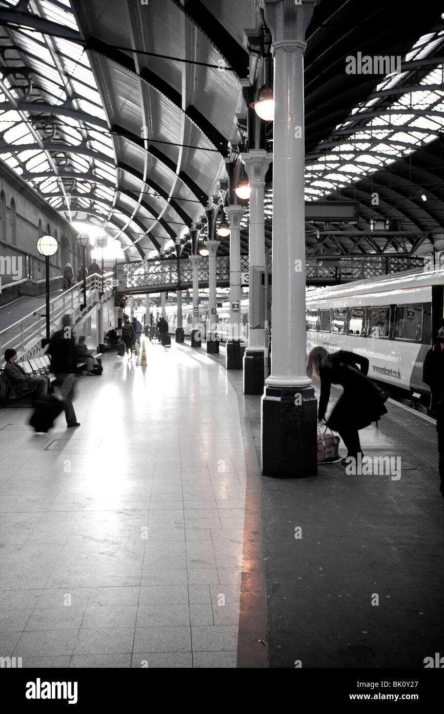 Newcastle railway station at sunset with people waiting for a train - Stock Image