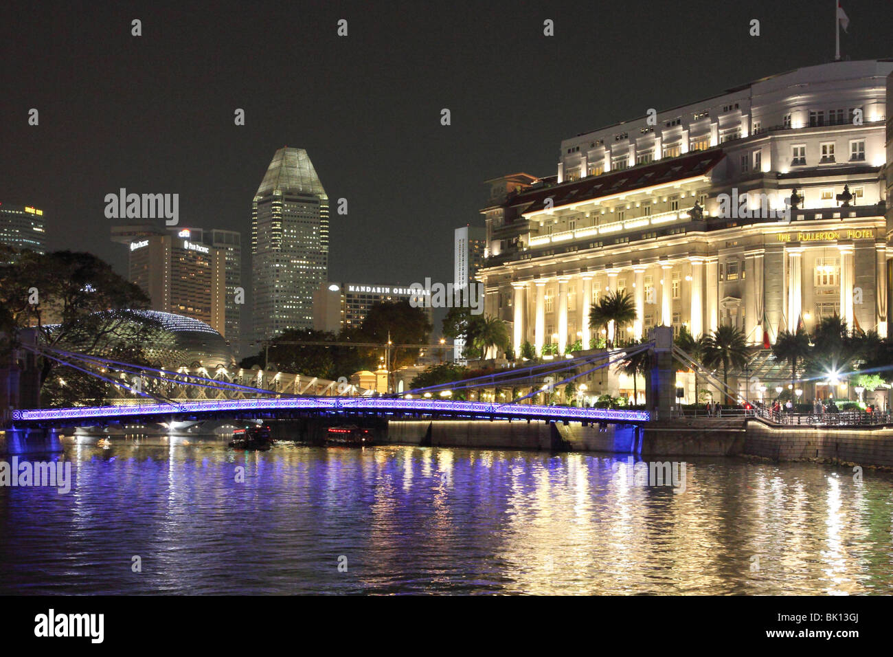 Night picture of the Fullerton Hotel with the Cavenagh bridge in the foreground, and Marina Quay in the background. - Stock Image