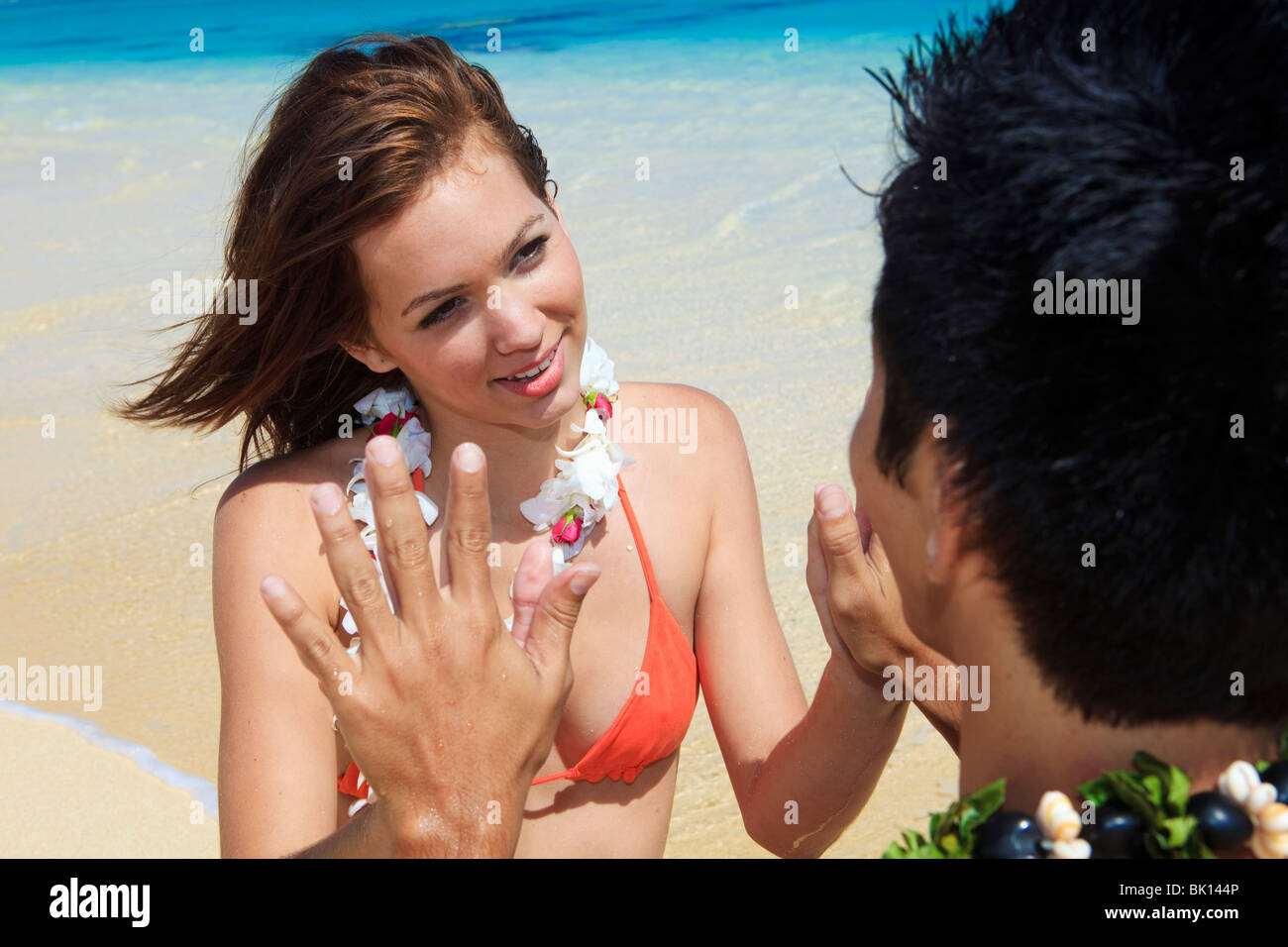 Pacific Island man and a young caucasian woman on the beach in Hawaii together and touch hands in a meditation and Stock Photo