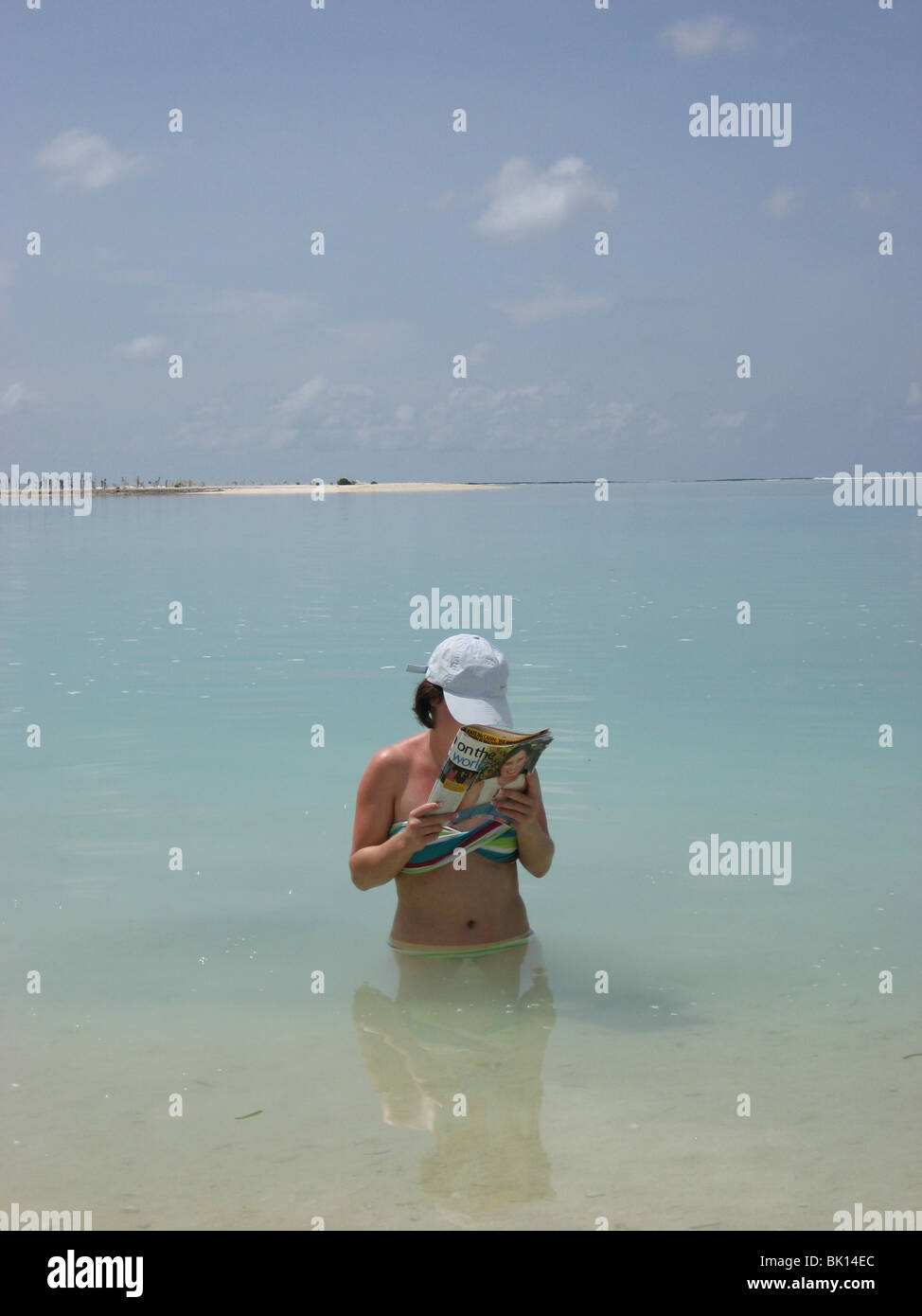 Young adult female reading a magazine while standing in a lagoon to keep cool - Stock Image