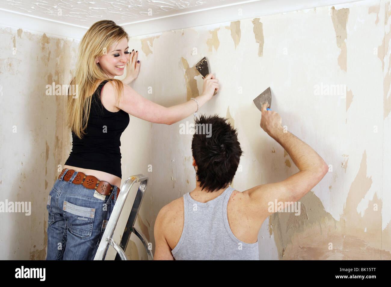 Young Couple Having Fun Stripping Wallpaper