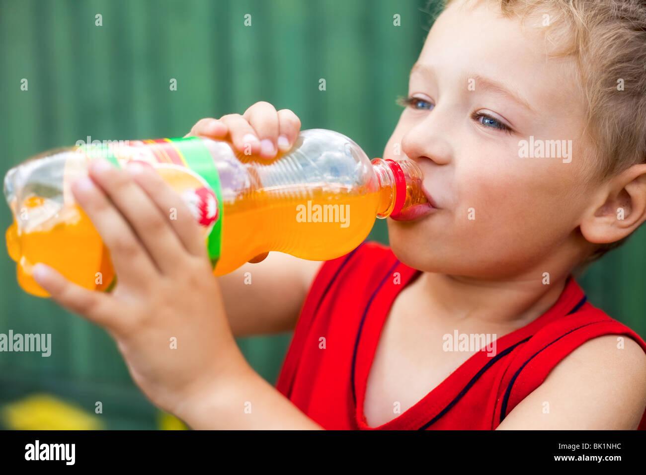 Little boy drinking unhealthy bottled soda - Stock Image