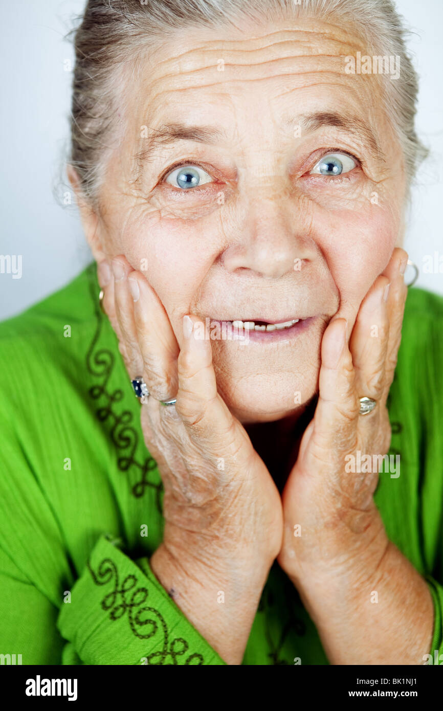 Excited senior woman with surprise expression on her face - Stock Image