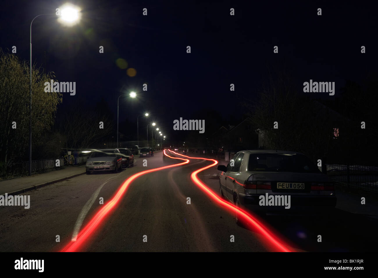 Light trails from the back of a car by night, long time exposure. - Stock Image