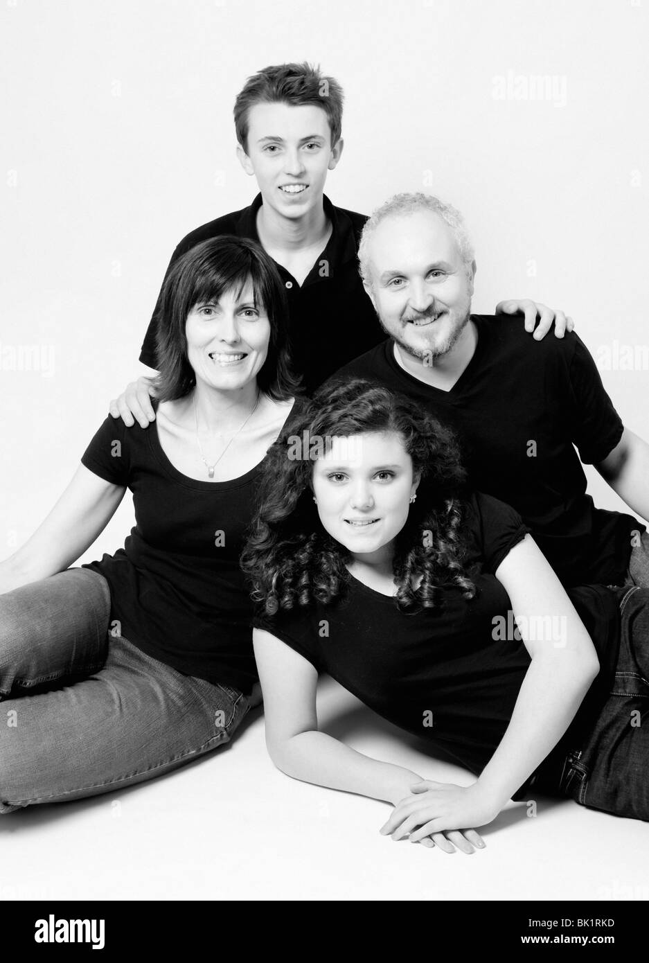 Studio family portrait of mum dad son daughter shot on white background