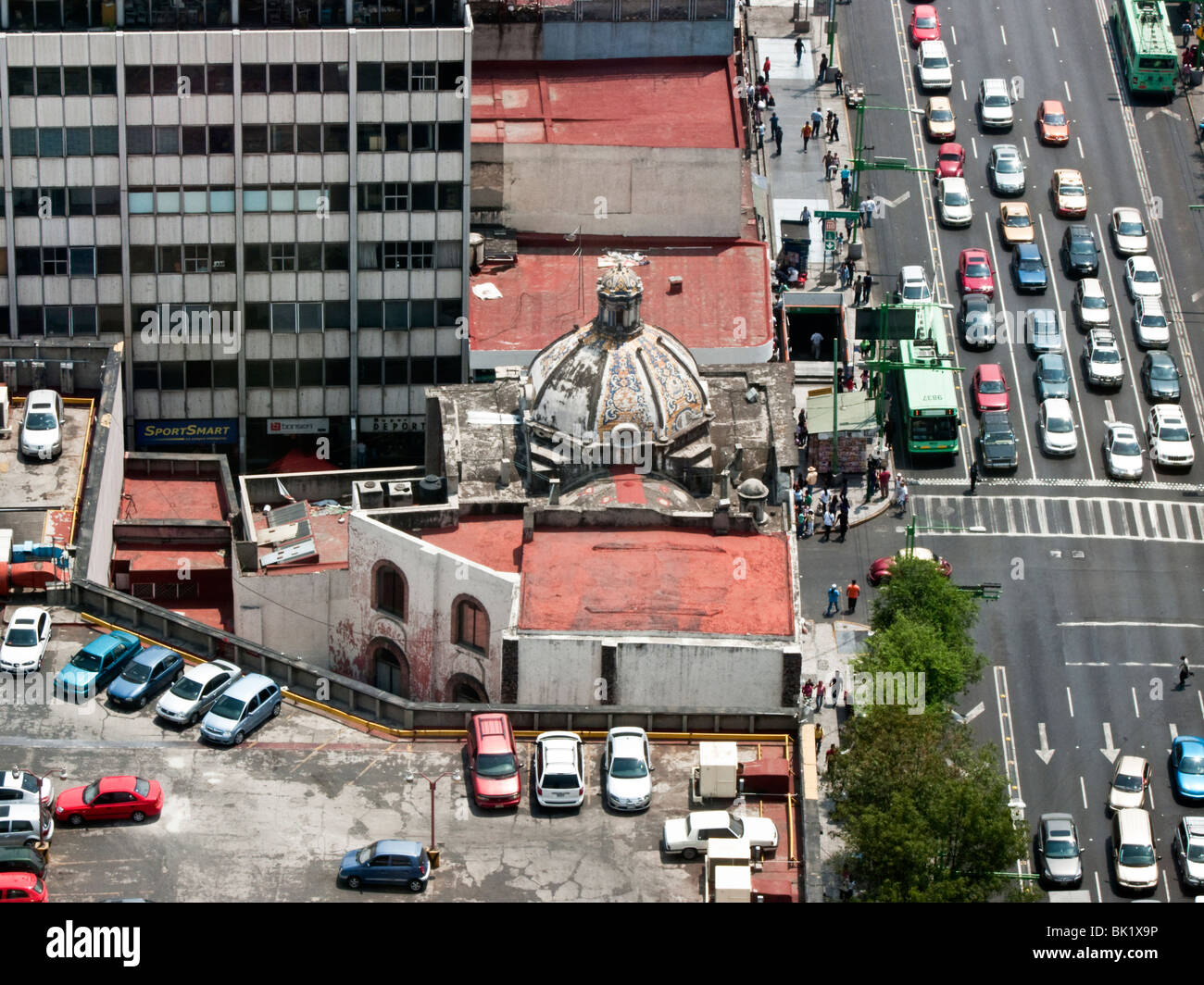 view looking down on traffic & electric buses on Avenida Laslo Cardenas & small old church sandwiched between large Stock Photo