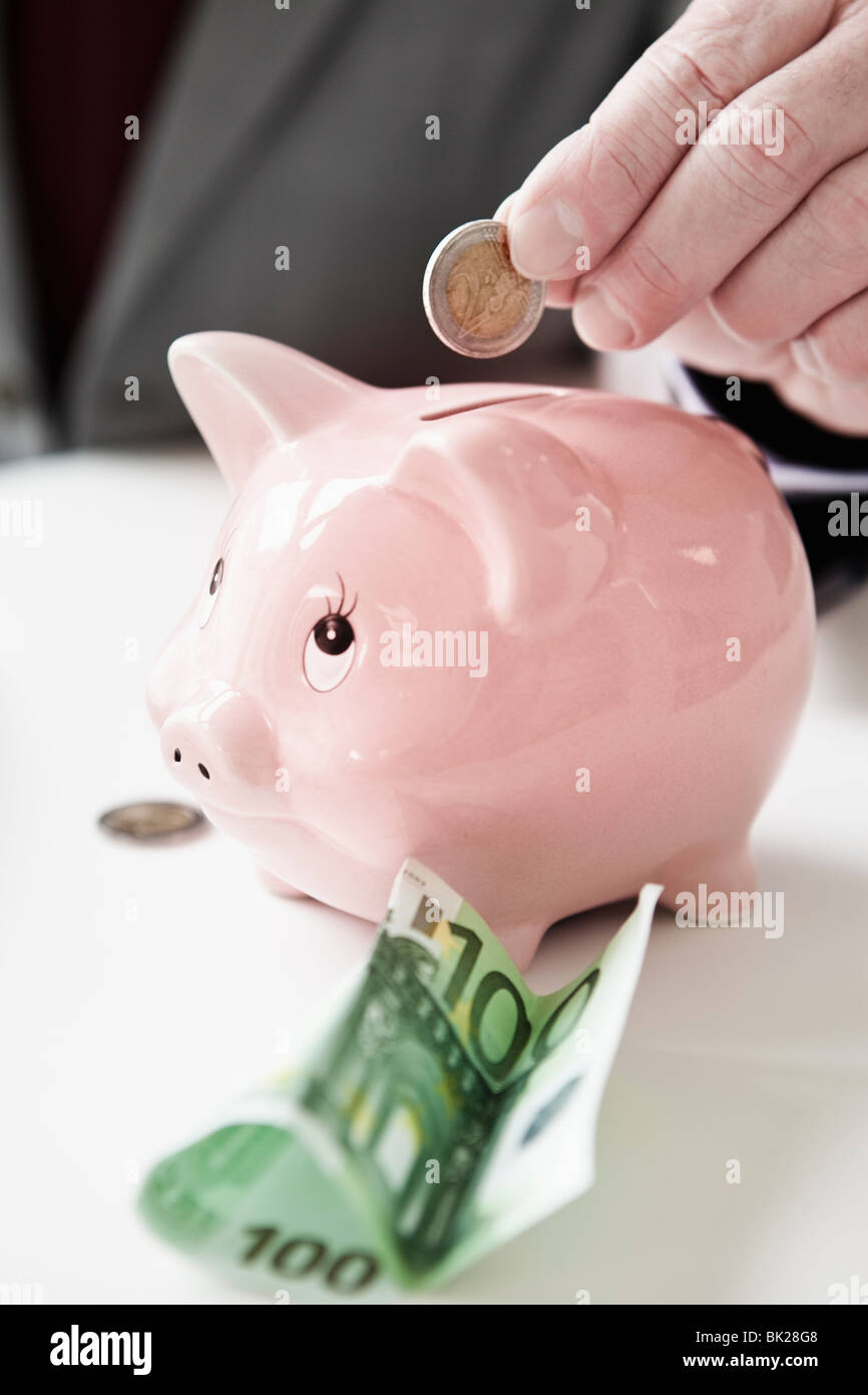 Hand putting coin into piggy bank - Stock Image
