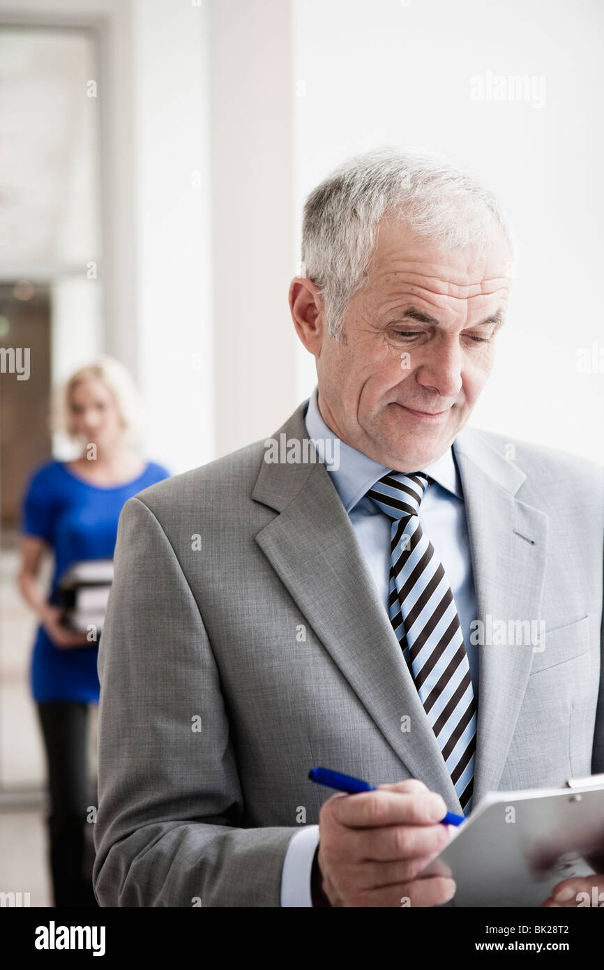 Businessman with clipboard - Stock Image