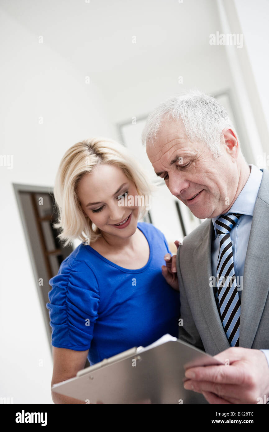 Businessman and woman with clipboard - Stock Image
