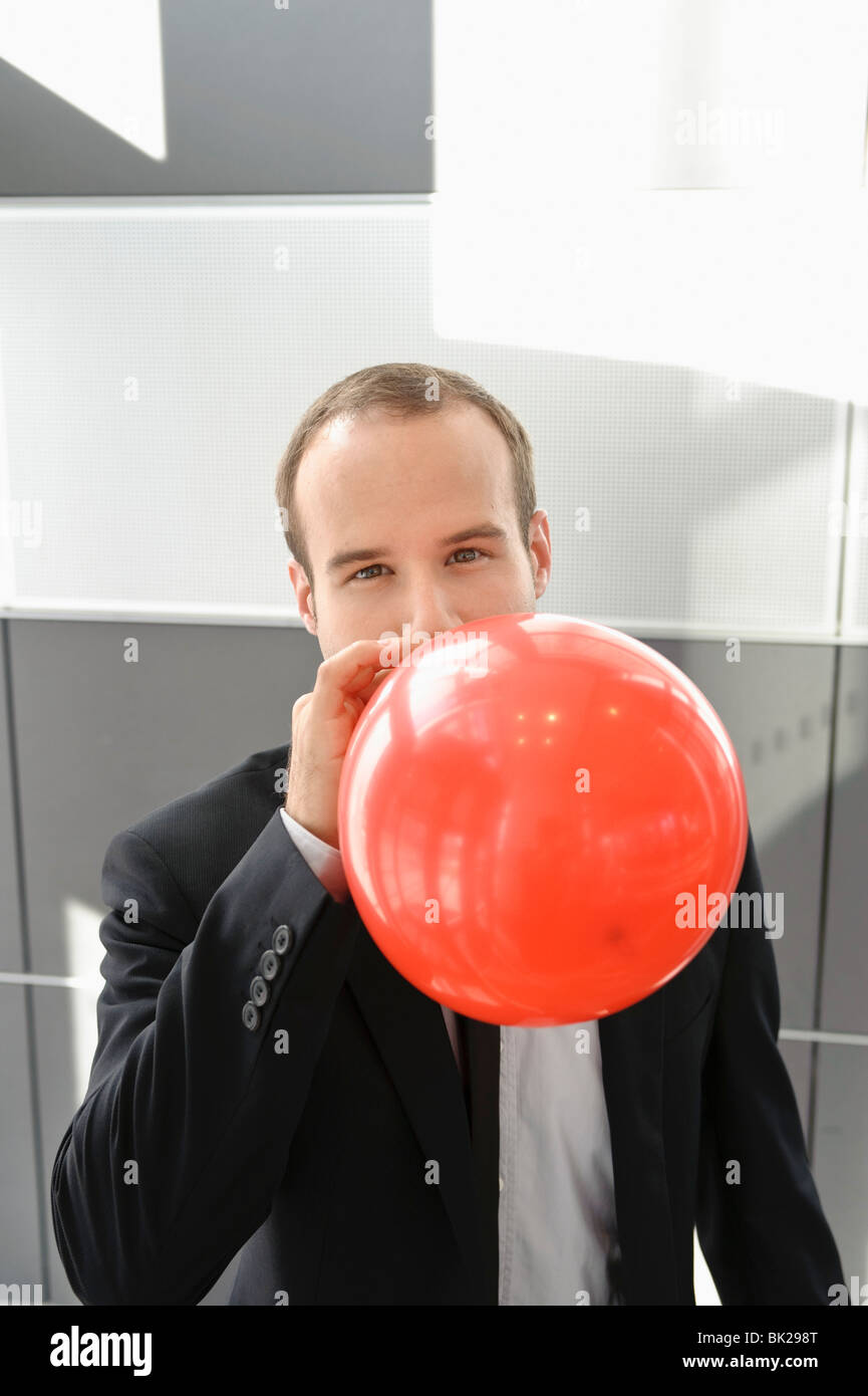 Businessman blowing up red balloon - Stock Image