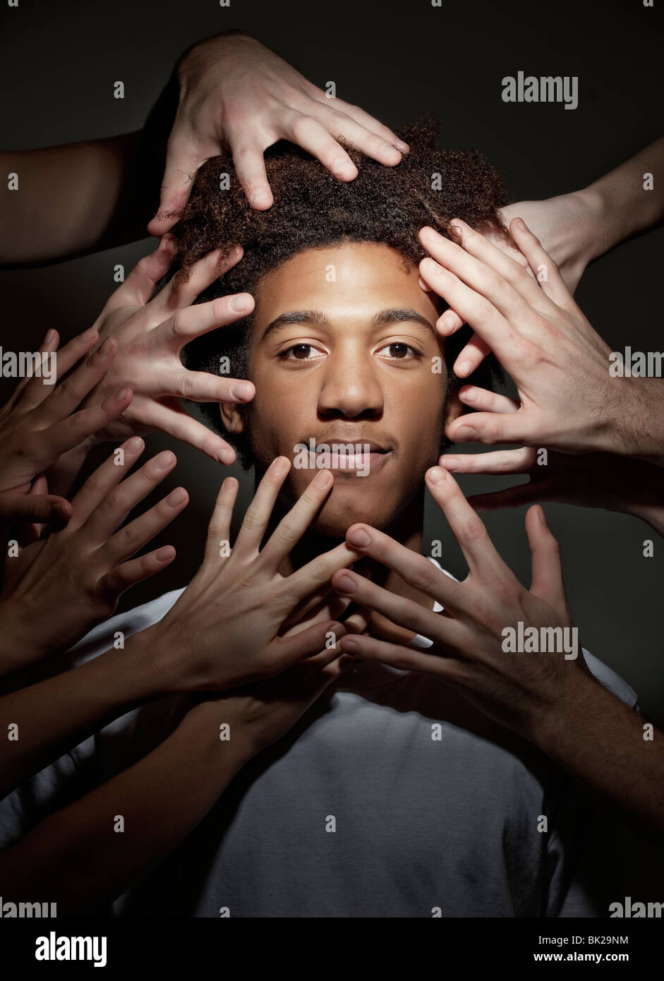 Black male surrounded by hands - Stock Image
