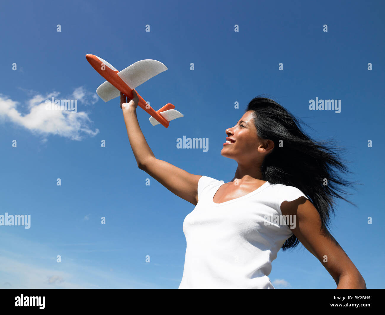 Woman holding a plane towards the sky - Stock Image