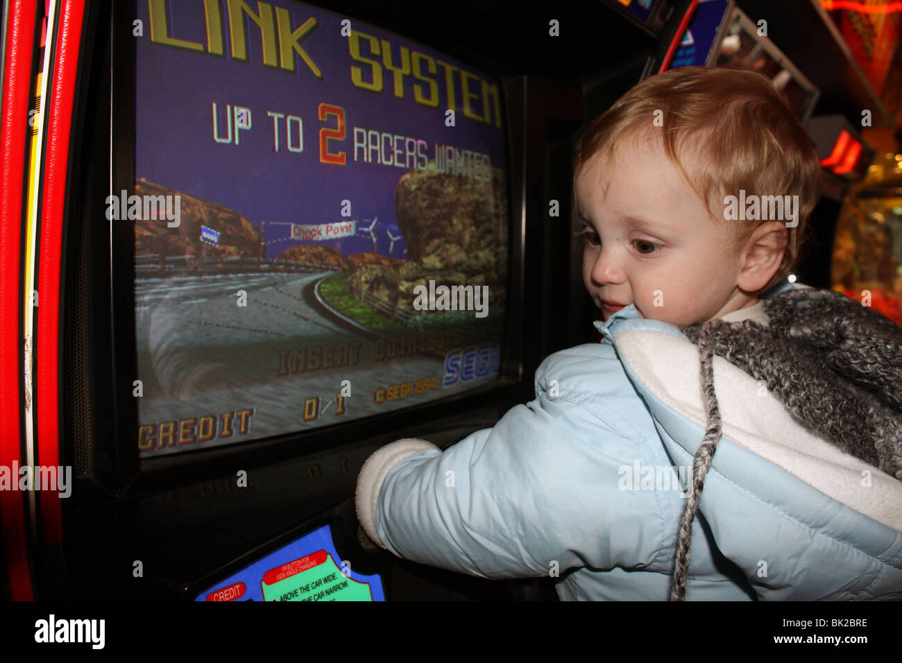 A young baby boy; just one year old entertaining himself by playing on a racing car game at the amusement arcade - Stock Image