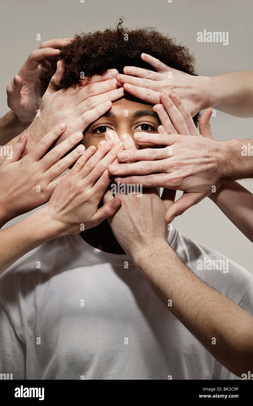 Black male hidden by hands - Stock Image