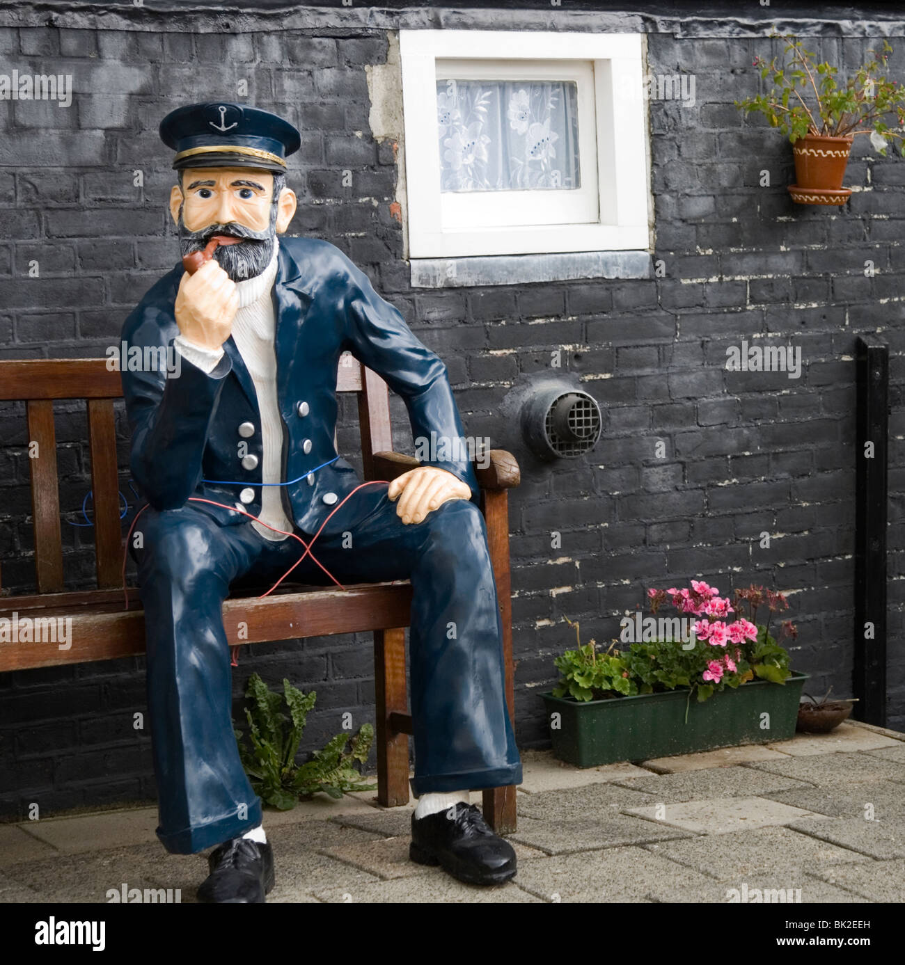 Navy blue statue of sailor sitting on a garden bench smoking a pipe. - Stock Image