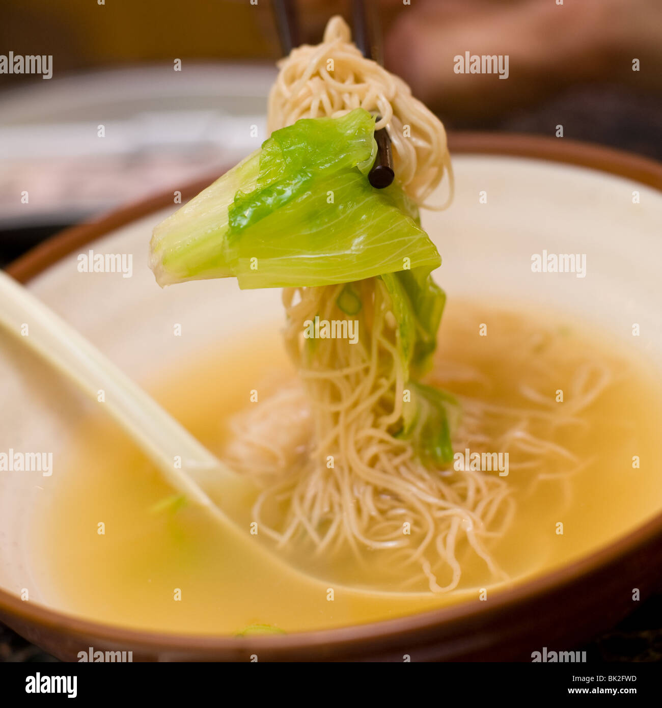Close up of shrimp wonton and noodle soup eaten with chopsticks at Chi Cafe in Chicago, IL - Stock Image