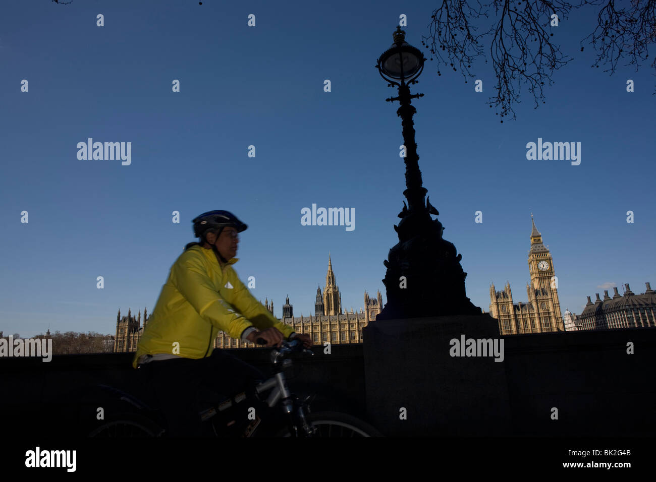 Elizabeth Tower amid the Gothic architecture of Britain's Houses of Parliament and cyclist on the Embankment - Stock Image